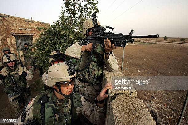 S Army soldiers of the 1st Battalion 503rd Infantry Regiment point a weapon at a distant target as they conduct a joint patrol with Iraqi commandos...