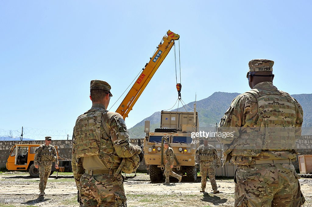 US Army soldiers of the 6th Kandak, 1st Brigade Combat Team, 101st Airborne Division (Air Assault) watch a crane place a cargo box on a military truck as part of the security transition from NATO to Afghan forces at Forward Base Honaker Miracle at Watahpur District in Kunar province on April 17, 2013. Budget cuts and war fatigue in Western capitals mean the 100,000 soldiers left serving in NATO's International Security Assistance Force are packing up and taking off as the mission prepares to close next year. AFP PHOTO/ Manjunath KIRAN