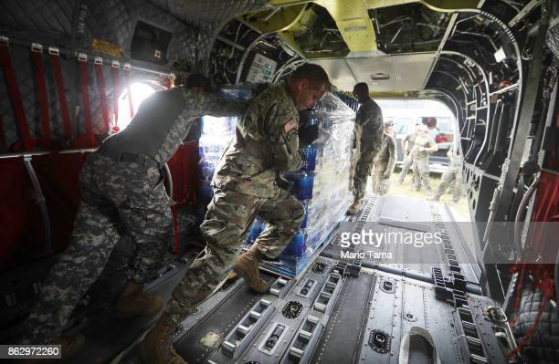 Army soldiers offload bottled water from a helicopter during recovery efforts four weeks after Hurricane Maria struck on October 18 2017 in Utuado...