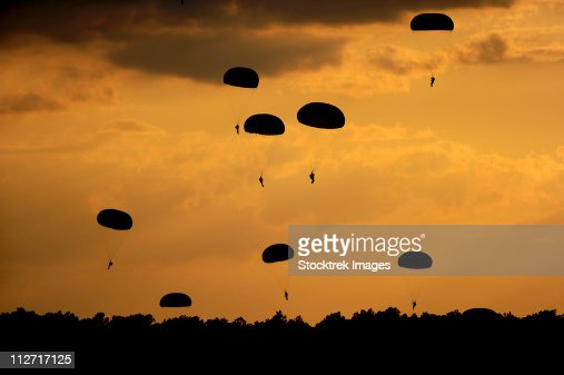 U.S. Army Soldiers parachute through the sky. : Stock Photo