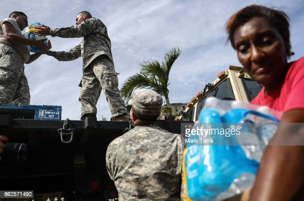 S Army soldiers pass out water provided by FEMA to residents in a neighborhood without grid electricity or running water on October 17 2017 in San...