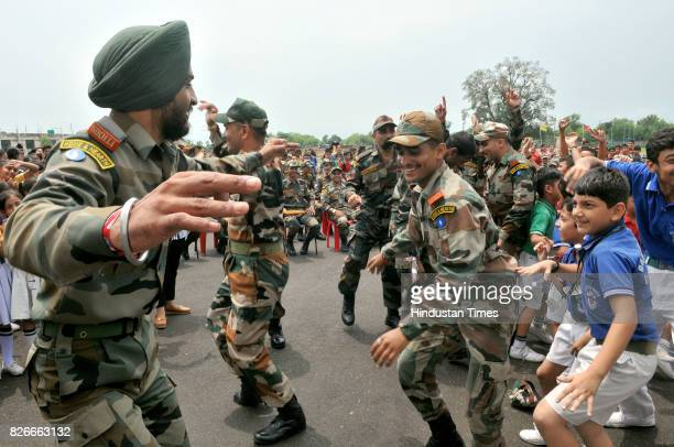 Army soldiers perform traditional Punjabi Bhangra dance as they celebrate Raksha Bandhan festival with students at a school in Kathua about 85 KM on...