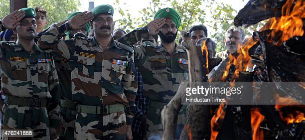 Army soldiers salute during the funeral procession of Lance Naik Kuldeep Raj who was killed in Ambush in Manipur at Ambh Gharota village in the...