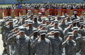 S Army soldiers salute during the national anthem before US President Barack Obama speaks at a memorial for victims of last week's shooting on the US...
