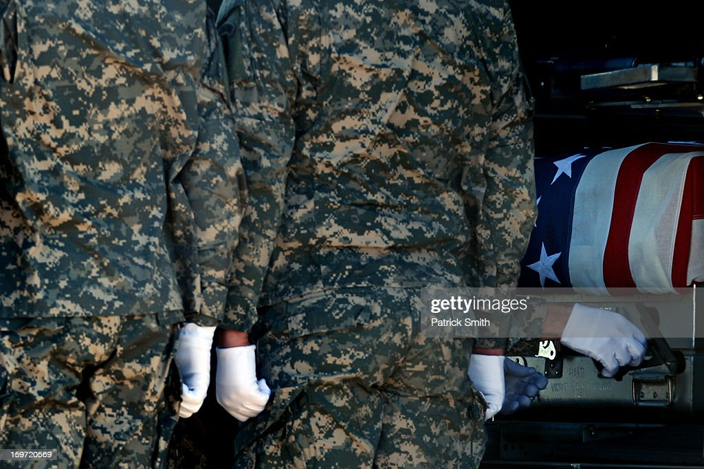 U.S. Army soldiers secure the flag-draped transfer case containing the remains of U.S. Army Sgt. David J. Chambers, during a dignified transfer at Dover Air Force Base, on January 19, 2013 in Dover, Delaware. Chambers, who was from Hampton, Va., was killed while supporting Operation Enduring Freedom.