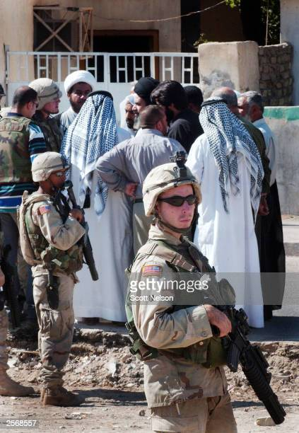 S Army soldiers stand guard as their commander negotiates with local Iraqi Shia clerics that have gathered to protest against the detention of local...