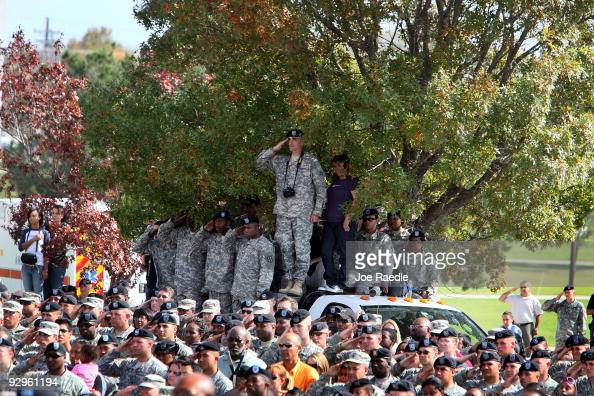 S Army soldiers stand together and salute during the playing of taps at the memorial service that US President Barack Obama and first lady Michelle...