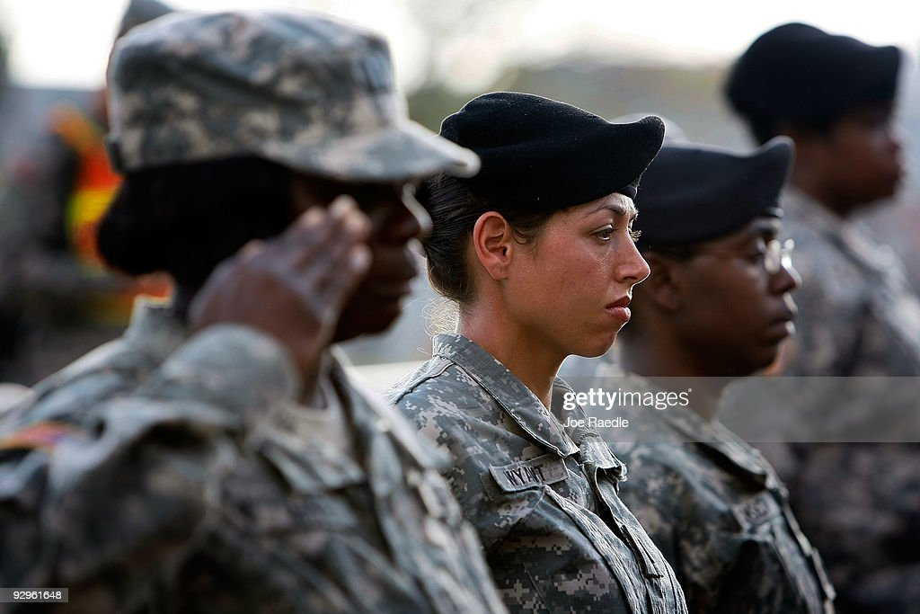 S Army soldiers stand together as they salute during the memorial service that US President Barack Obama and first lady Michelle Obama attended in...