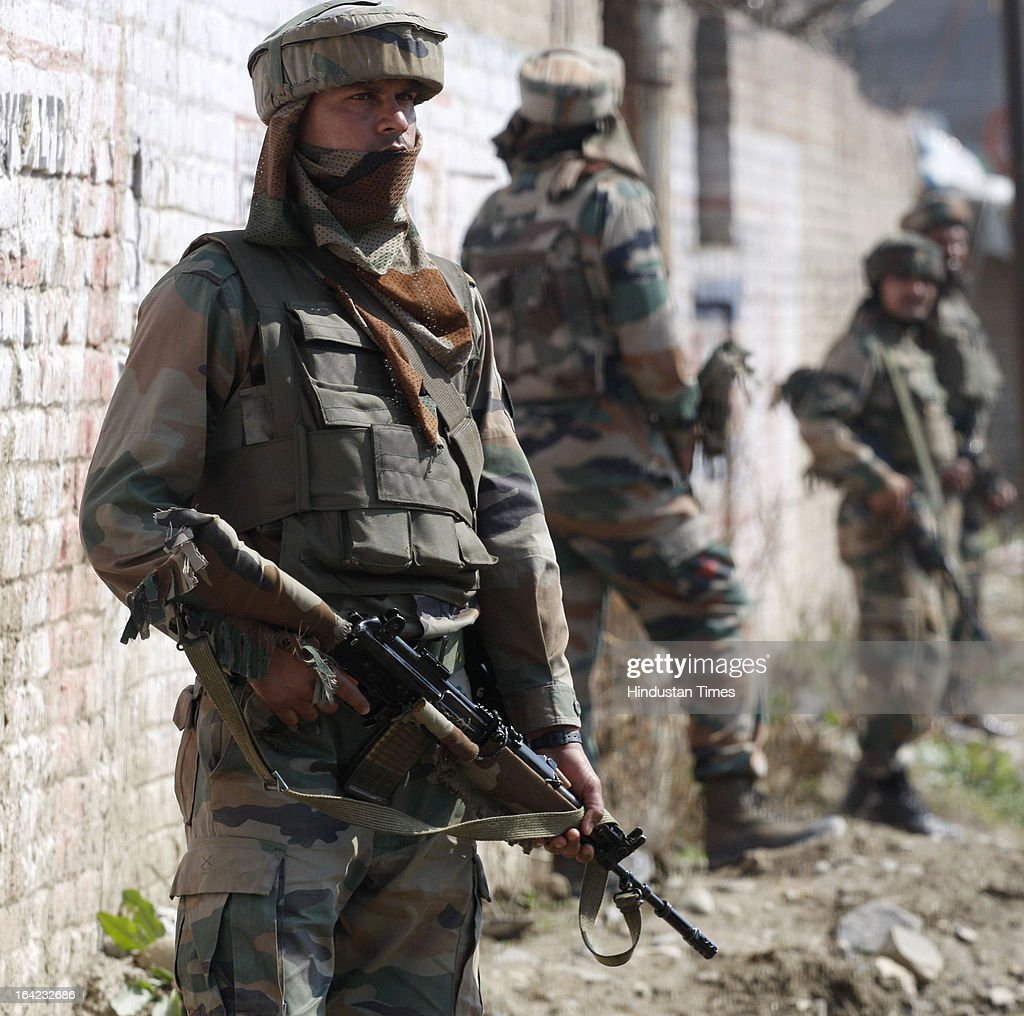 Army soldiers take position near the site of a shootout after militants attacked a Border Security Force (BSF) convoy at Nowgam Srinagar- Jammu National Highway, on March 21, 2013 in Srinagar, India. Three BSF jawans were injured in the attack.