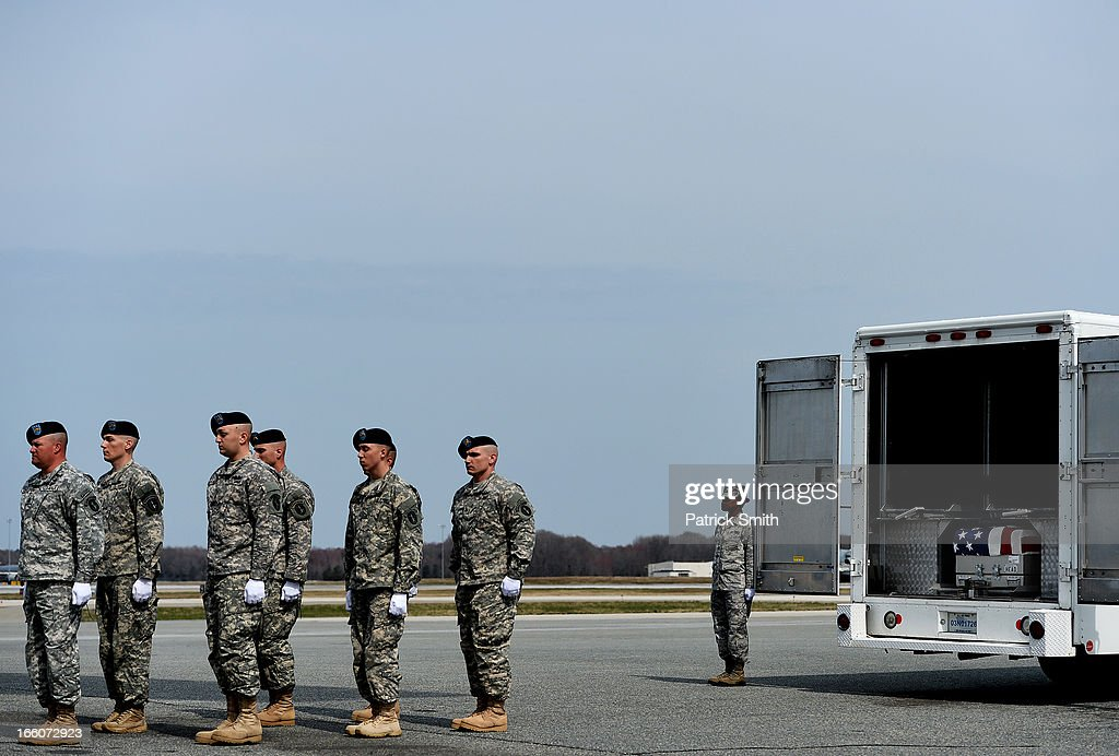 U.S. Army soldiers walk away from the transfer vehicle after they placed the flag-draped transfer cases containing the remains of Department of Defense Civilian Hyun K. Shin and U.S. Army Staff Sgt., Christopher M. Ward during a dignified transfer at Dover Air Force Base, on April 8, 2013 in Dover, Delaware. Shin, who was from Hesperia, Calif., was killed while supporting U.S. Army Corps of Engineers Operation Enduring Freedom - Afghanistan, and Ward, who was from Oak Ridge, Tenn., was killed while supporting Operation Enduring Freedom - Afghanistan.