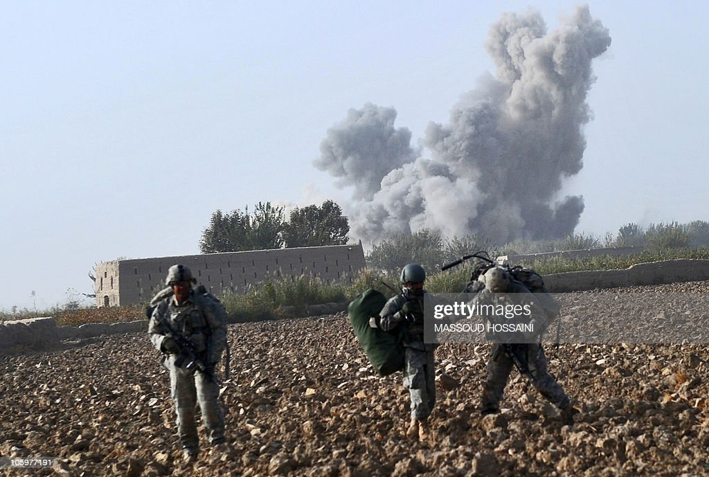 US Army soldiers walk through a field on a patrol as an explosion occurs in Zari District of Kandahar province on October 23 2010 More than 150000 US...