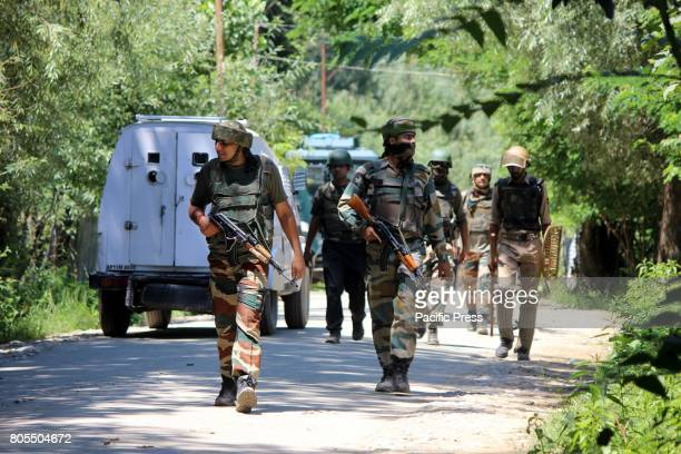 DAILGAM ANANTNAG JANMMU KASHMIR INDIA Army soldiers walk towards the encounter site at Dailgam area of South Kashmir's Anantnag Indian controlled...