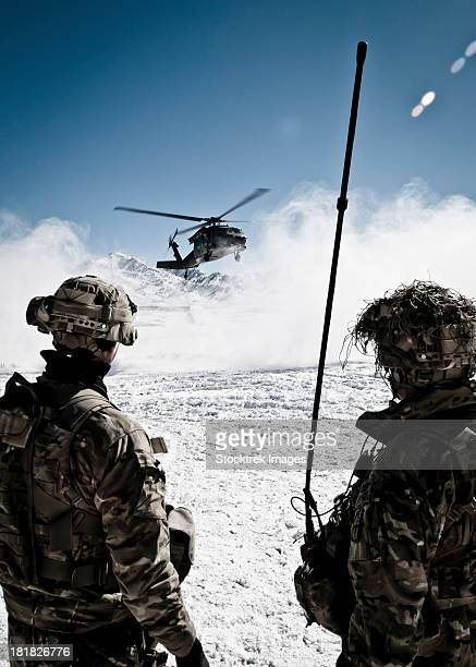 U.S. Army soldiers watch the arrival of a helicopter at an outpost in Afghanistan.
