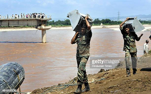 Army soldiers working on reconnecting the damaged bridge over Tawi River at Barjala village on September 8 2014 on the outskirts of Jammu India The...