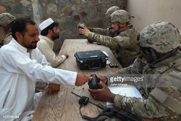 S Army soliers record biometric data from men entering Afghanistan at the border crossing with Pakistan August 27 2011 at Torkham Afghanistan The...