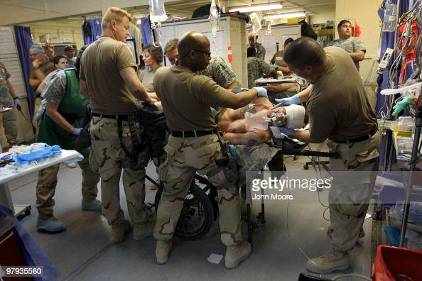 US Army Spc Benjamin McCune is turned on his side as medical personel check him for wounds at the military hospital on March 22 2010 at Kandahar...