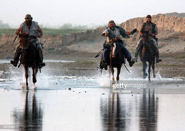 S Army Special Forces soldiers gallop down a shallow riverbed during a horseback presence patrol through the town of Kunduz August 25 2002 in...