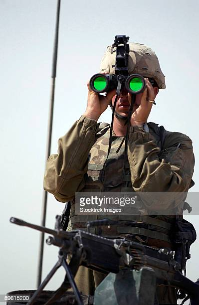 US Army Specialist, armed with a 5.56mm M249 Suad Automatic Weapon, uses binoculars to scan the perimeter as he mans his perimeter defense to the company's assembly area at Balad, Iraq, during Operation Iraqi Freedom.