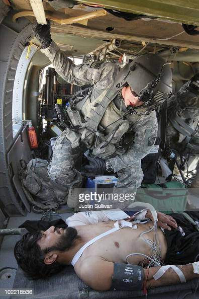 S Army specialist David Harrell of Charlie Co Sixth Battalion 101st Airborne Combat Aviation Brigade Task Force Shadow monitors an Afghan man who was...