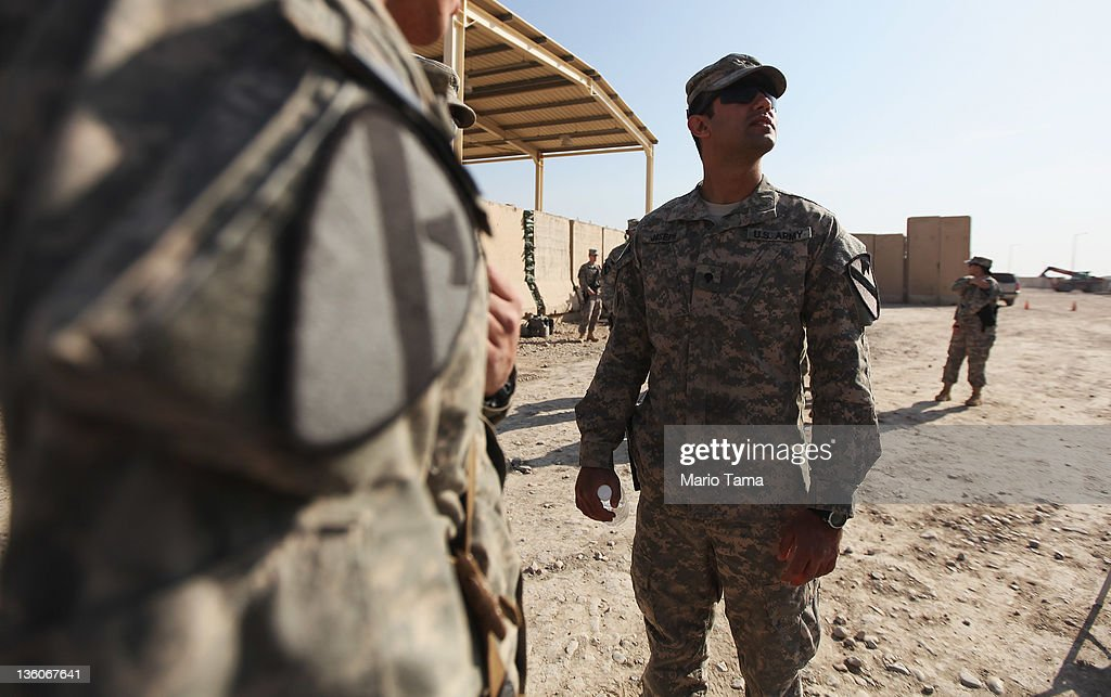 U.S. Army specialist Joseph (not real name) looks on after a casing of the colors ceremony at Camp Adder, now known as Imam Ali Base, on December 17, 2011 near Nasiriyah, Iraq. Specialist Joseph worked as an Iraqi interpreter for the U.S. military in Baghdad from 2003-2008 before moving to the U.S. in 2009 and enlisting in the military in 2010. Joseph deployed to Iraq in early 2011 and has become a U.S. citizen. Around 500 troops from the 3rd Brigade, 1st Cavalry Division ended their presence on Camp Adder, the last remaining American base, and departed in the final American military convoy out of Iraq, arriving into Kuwait in the early morning hours of December 18, 2011. All U.S. troops were scheduled to have departed Iraq by December 31st, 2011. At least 4,485 U.S. military personnel died in service in Iraq. According to the Iraq Body Count, more than 100,000 Iraqi civilians have died from war-related violence.