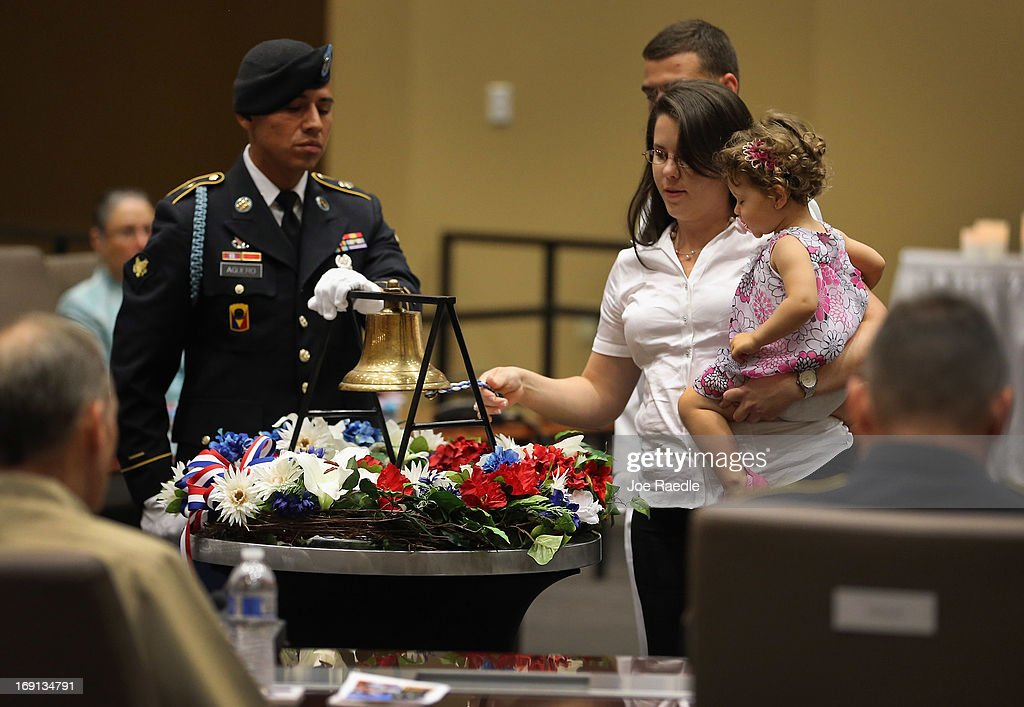 U.S. Army Specialist Juan Aguero, from the Florida National Guard Honor Guard, stands beside a bell as Joanna Gonzalez holds her daughter, Ayeleth Garces while ringing the bell in honor of her husband during a ceremony to remember and honor those who have died in service to the nation and the families they have left behind at U.S. Southern Command headquarters on May 20, 2013 in Doral, Florida. U.S. Marine Gen. John Kelly presided over the ceremony where the families of 57 fallen service members from South Florida were invited to attend.