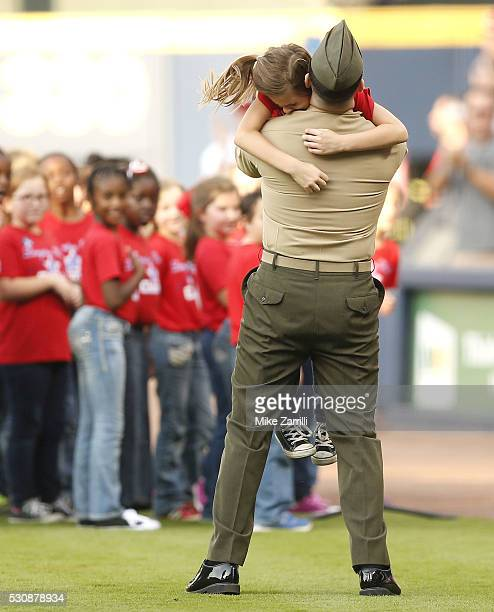S Army staff sergeant Clayton Walker surprises his daughter Cassidy after an 11 month assignment overseas on the field after Cassidy sang the...