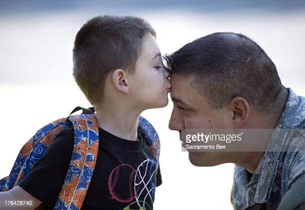 US Army Staff Sgt Edward Mattey gets a goodbye kiss from his son Giovanni Mattey on his first day of school at Folsom Hills Elementary School on...