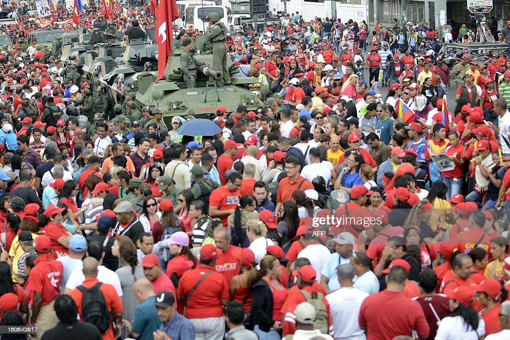 Army tanks and supporters of the Venezuelan President Hugo Chavez take to the streets to conmemorate the 1992 failed coup led by Chavez, who was an army lieutenant colonel, against then president Carlos Andres Perez, in Caracas, on February 4, 2013. Ailing President Hugo Chavez, who had cancer surgery in December, is doing much better and recovering, Cuban leader Fidel Castro said in remarks published Monday. AFP PHOTO/Leo RAMIREZ
