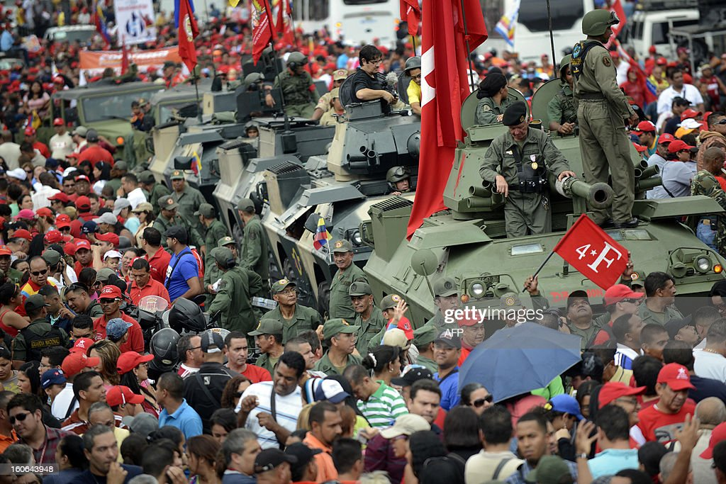 Army tanks are surrounded by supporters of the Venezuelan President Hugo Chavez during a march to conmemorate the 1992 failed coup led by Chavez, who was an army lieutenant colonel, against then president Carlos Andres Perez, in Caracas, on February 4, 2013. Ailing President Hugo Chavez, who had cancer surgery in December, is doing much better and recovering, Cuban leader Fidel Castro said in remarks published Monday. AFP PHOTO/Leo RAMIREZ