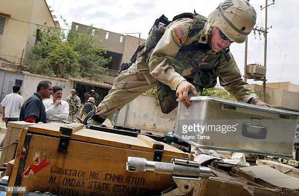 S Army Third Infantry Division soldier loads materials discovered in an explosives laboratory hidden in a home April 15 2003 in Baghdad Iraq Military...