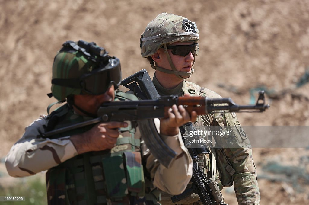 S Army trainer watches as an Iraqi recruit fires at a military base on April 12 2015 in Taji Iraq US forces currently operating in 5 large bases...