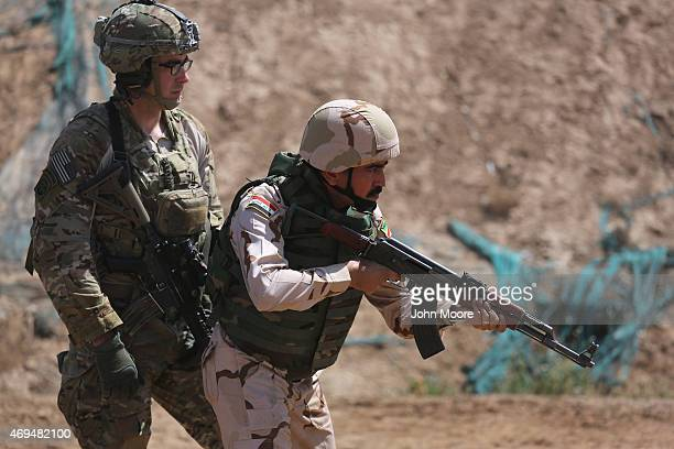 S Army trainer watches as an Iraqi recruit prepares to fire at a military base on April 12 2015 in Taji Iraq US forces currently operating in 5 large...