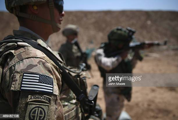 S Army trainers watch as an Iraqi recruit fires at a military base on April 12 2015 in Taji Iraq US forces currently operating in 5 large bases...