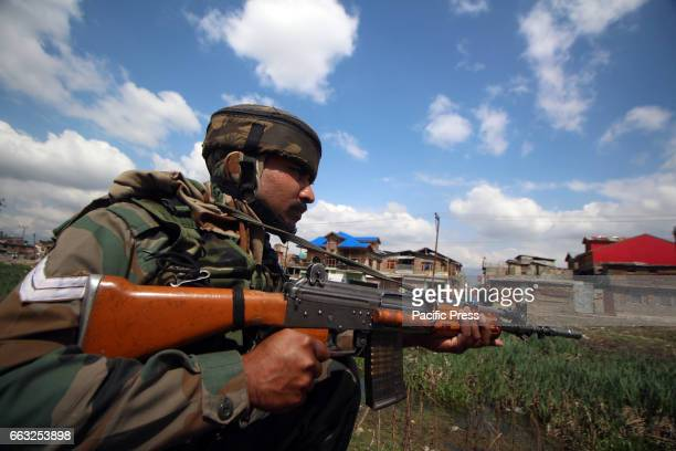Army trooper taking positions after the suspected militants carried out an ambush on their convoy in Bemina area of Srinagar in Indian Controlled...