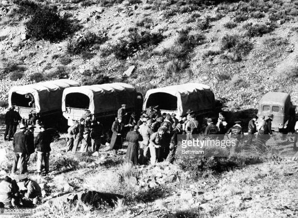 Army trucks and ambulances are shown being unloaded by the Army searching party at a point five miles from the scene of the air crash that took the...