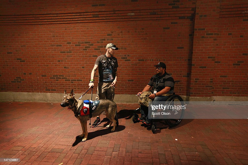 Army veteran Brad Schwarz (L), with his service dog Panzer, chats with Marine Corps veteran James Dahan while they smoke cigarettes outside Wrigley Field during a Chicago Cubs game on June 14, 2012 in Chicago, Illinois. Dahan was injured while serving in Iraq in 2004. Schwarz uses Panzer to help him cope with post-traumatic stress disorder (PTSD) related to his 2008 tour in Iraq. In addition to suffering from PTSD Schwarz has memory loss related to Traumatic Brain Injury (TBI) and he must walk with a cane because of vertebrae and nerve damage in his back and legs. Ten days before he was scheduled to rotate home from a 15-month deployment in Iraq, his second, the Humvee in which he was riding was struck by an Improvised Explosive Device (IED). Of the 5 soldiers riding in the vehicle, which caught fire after the explosion, Schwarz was the only one to survive.