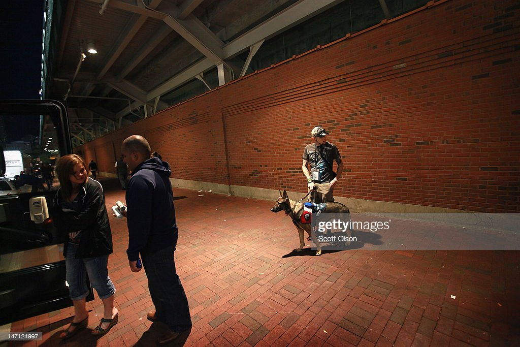 Army veteran Brad Schwarz, with his service dog Panzer, leaves a Chicago Cubs' game which he was attending with a group of veterans from the Wounded Warrior Project at Wrigley Field on June 14, 2012 in Chicago, Illinois. Schwarz uses Panzer to help him cope with post-traumatic stress disorder (PTSD) issues related to his 2008 tour in Iraq. In addition to suffering from PTSD Schwarz has memory loss related to Traumatic Brain Injury (TBI) and he must walk with a cane because of vertebrae and nerve damage in his back and legs. Ten days before he was scheduled to rotate home from a 15-month deployment in Iraq, his second, the Humvee in which he was riding was struck by an Improvised Explosive Device (IED). Of the 5 soldiers riding in the vehicle, which caught fire after the explosion, Schwarz was the only one to survive.