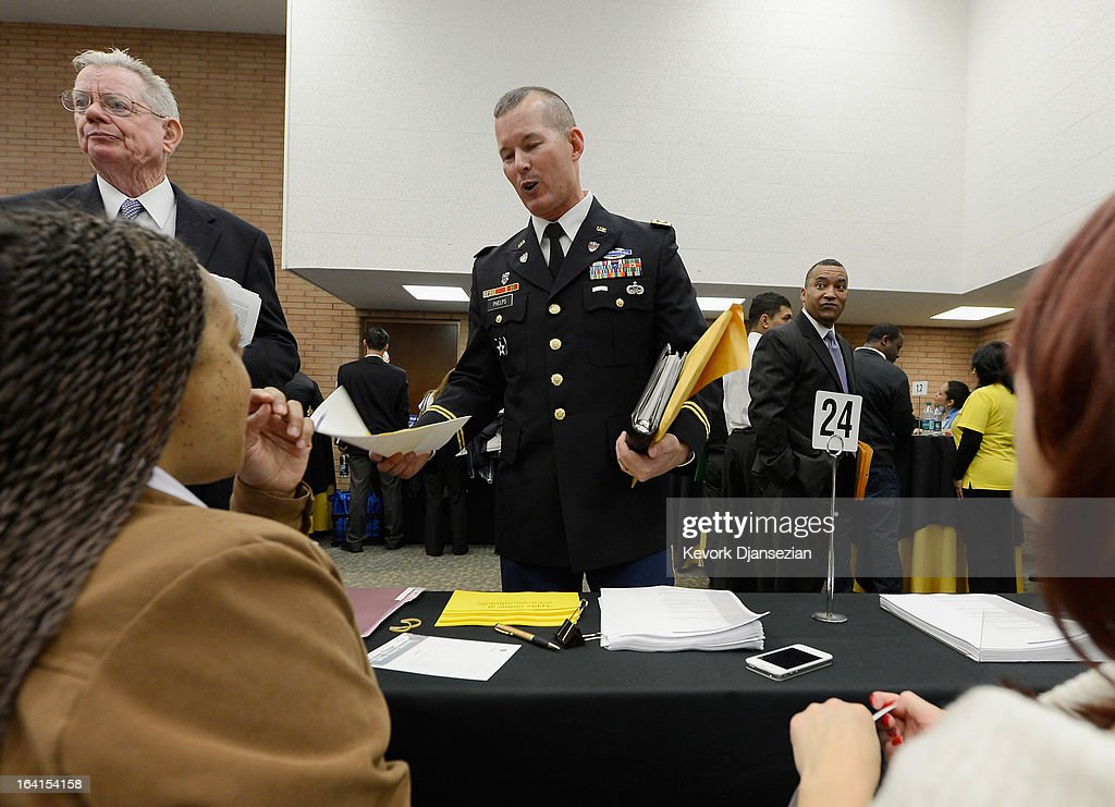 S Army veteran Col Shawn Phelps speaks with job recruiters at the University of Southern California booth during a jobs fair for veterans called...