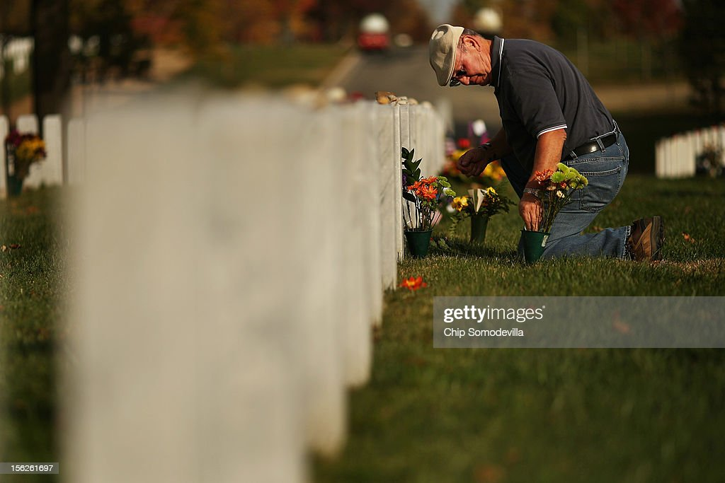 U.S. Army veteran Francis Adamouski of Fairfax, Virginia, places flowers at the grave of his son, Army Captain James F. 'Jimmy' Adamouski, in Section 60 at Arlington National Cemetery November 12, 2012 in Arlington, Virginia. A veteran of the Vietnam war with more than 23 years of military service, Adamouski's son was the first West Point graduate to die in Iraq when his helicopter crashed April 2, 2003.