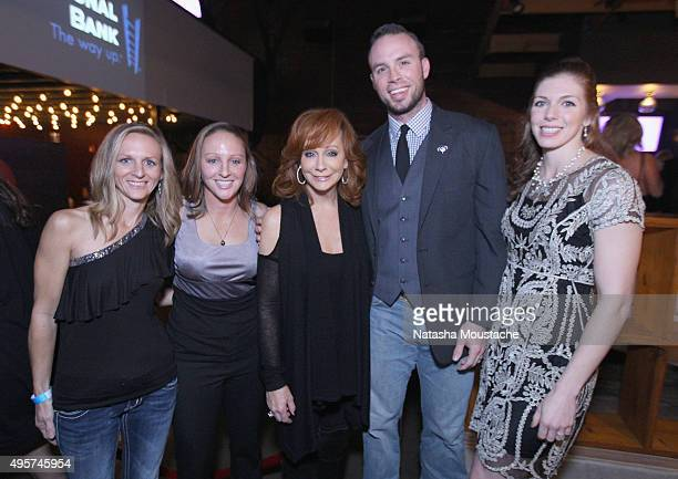S Army Veterans Leigh Ann Hester and Dallas Robinson pose with Reba McEntire at the Big Machine Label Group CMA Awards AfterParty in Nashville Tenn...