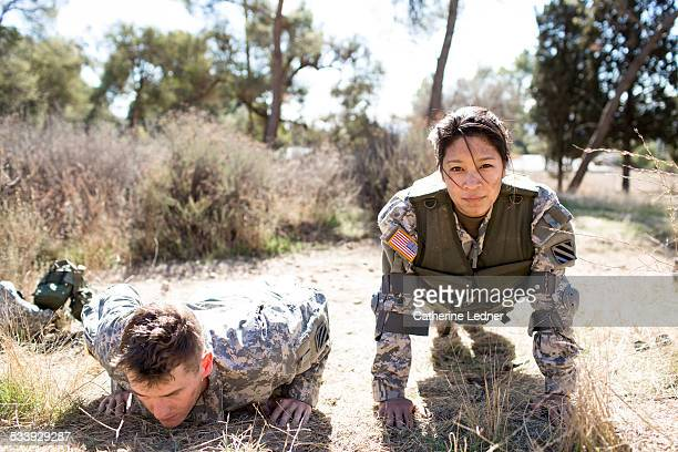 Army woman and man doing pushups
