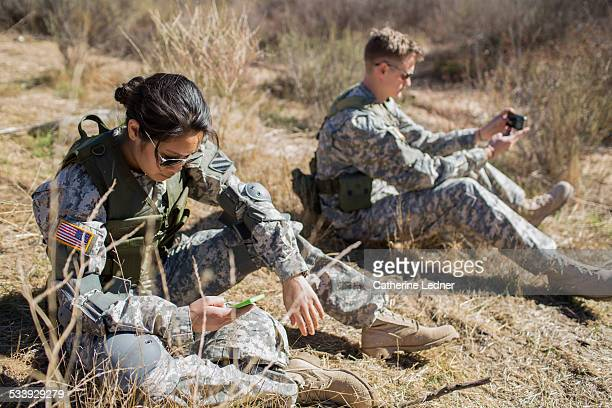 Army woman and man looking at their phones