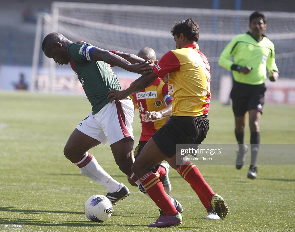 Arnab Mondal (R) of East Bengal is trying to hold Odafa (L) of Mohun Bagan from back during the derby match of I-League at Yuba Bharati Krirangan, Salt Lake on February 9, 2013 in Kolkata, India.