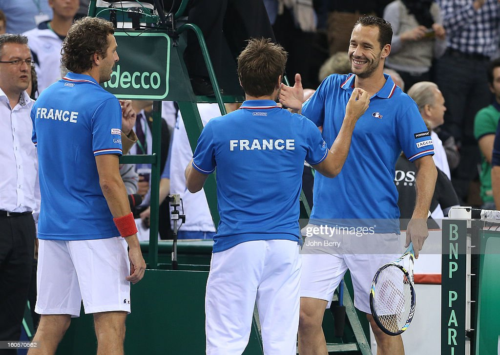 Arnaud Clement, coach of France congratulates Julien Bennetteau and teammate Michael Llodra of France after their victory in the doubles match against Jonathan Erlich and Dudi Sela of Israel on day two of the Davis Cup first round match between France and Israel at the Kindarena stadium on February 2, 2013 in Rouen, France.