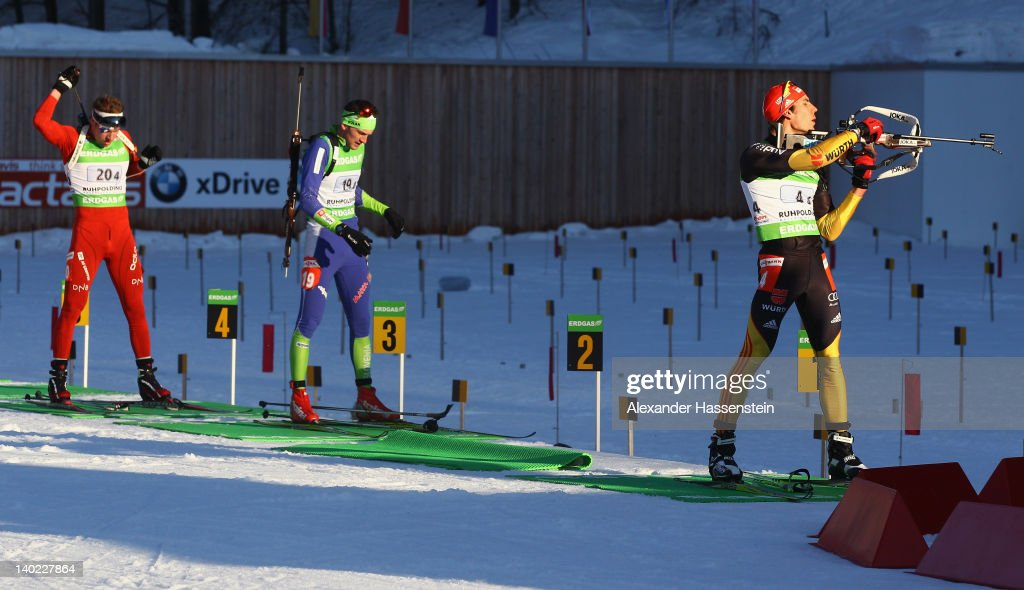 Arnd Peiffer of Germany comeptes at the shooting range with Jakov Fak of Slovenia and Emil Hegle Svendsen of Norway comeptes during the IBU Biathlon...