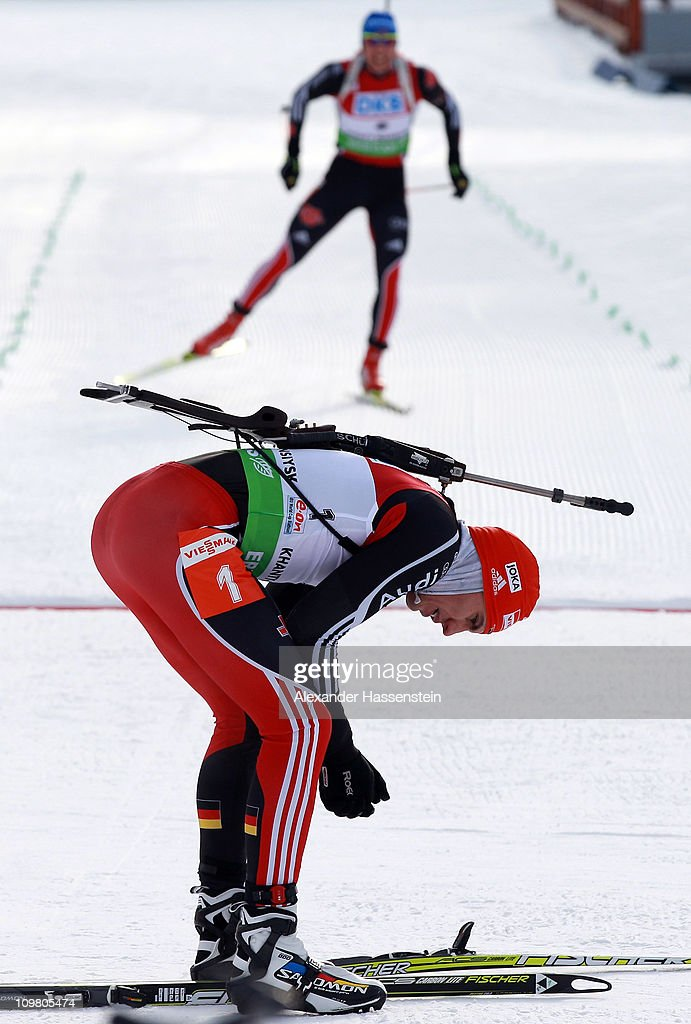 Arnd Peiffer of Germany reacts at the finish area whilst his team mate Andreas Birnbacher crosses the finish line at the men's 12,5km pursuit during the IBU Biathlon World Championships at A.V. Philipenko winter sports centre on March 6, 2011 in Khanty-Mansiysk, Russia.