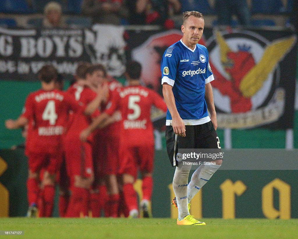 <a gi-track='captionPersonalityLinkClicked' href=/galleries/search?phrase=Arne+Feick&family=editorial&specificpeople=808586 ng-click='$event.stopPropagation()'>Arne Feick</a> (R) of Bielefeld looks dejected while players of Leverkusen celebrate their teams first goal during the DFB Cup match between Arminia Bielefeld and Bayer 04 Leverkusen at Schueco Arena on September 24, 2013 in Bielefeld, Germany.