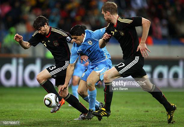 Arne Friedrich and Per Mertesacker of Germany challenge Luis Suarez of Uruguay during the 2010 FIFA World Cup South Africa Third Place Playoff match...