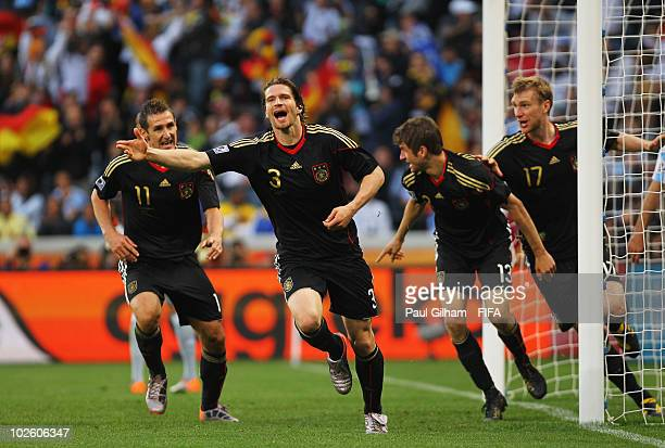 Arne Friedrich of Germany celebrates scoring the third goal with teammates Miroslav Klose Thomas Mueller and Per Mertesacker during the 2010 FIFA...