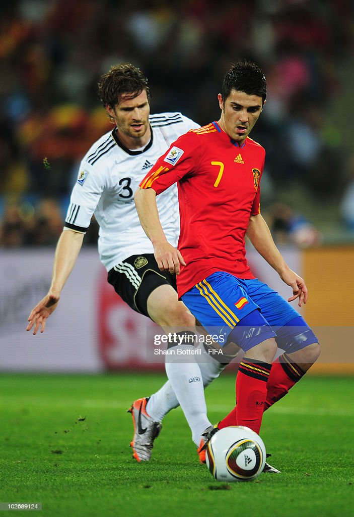Arne Friedrich of Germany vies for the ball with David Villa of Spain during the 2010 FIFA World Cup South Africa Semi Final match between Germany...
